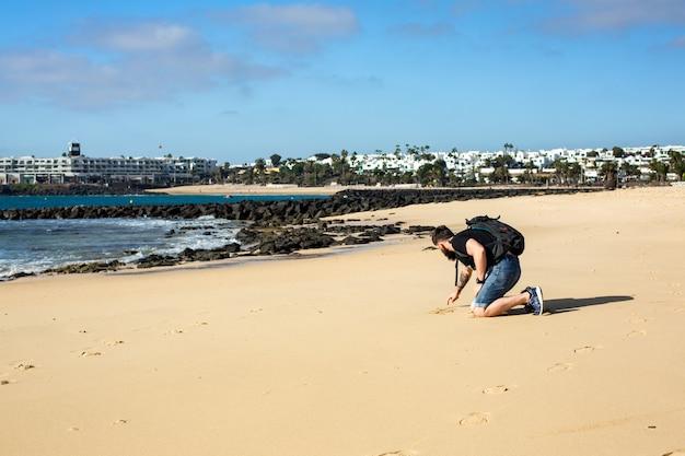 Een man tekent bij eb in de ochtend op het zand. strand in costa teguise. eiland lanzarote, spanje.