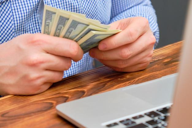 Een man telt winst in de vorm van geld van het bedrijf voor de laptop.