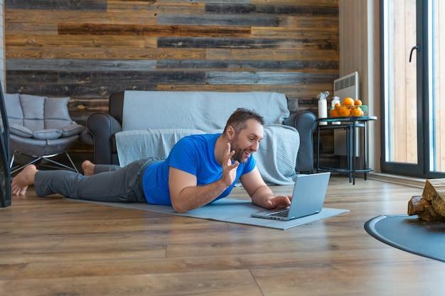 Een man tijdens een online videogesprek. hij ligt op de grond terwijl hij voor een laptopmonitor staat. hij zwaait met zijn hand en zegt hallo.