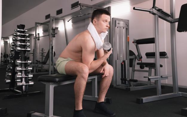 Een man tilt halters op in de fitnessruimte. een man sport in een sportcentrum. een persoon geeft om zijn gezondheid. blote romp