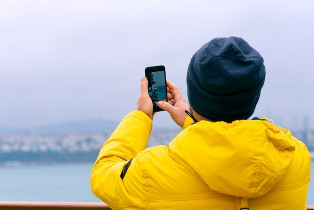 Een man-toerist die telefonisch een foto neemt op het uitzichtpunt vóór de bosporus in istanbul