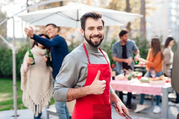 Een man toont duim tijdens het koken van groenten op de grill.