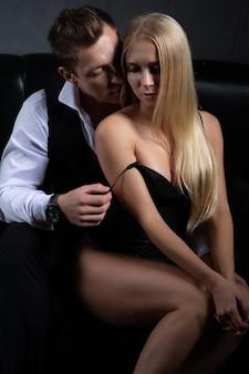 Een man trekt een jurk uit van zijn charmante vrouw die naast hem op de bank zit