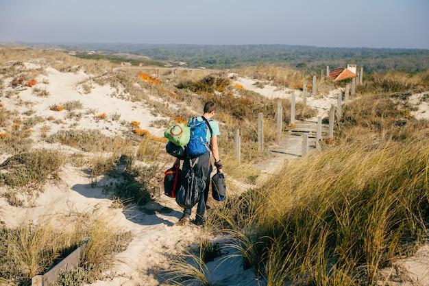 Een man van achteren die door zandduinen loopt met veel tassen