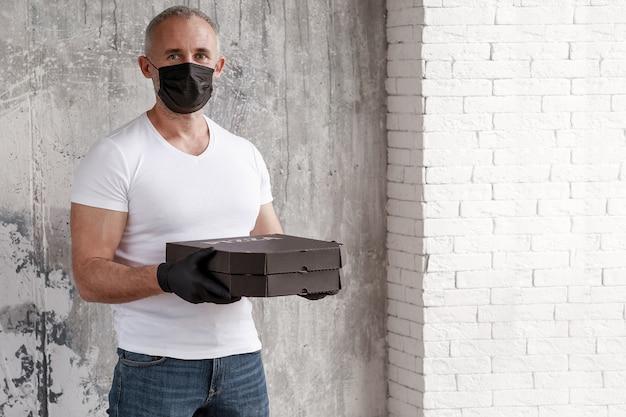 Een man van een pizzakoerier in een zwart medisch masker en zwarte handschoenen