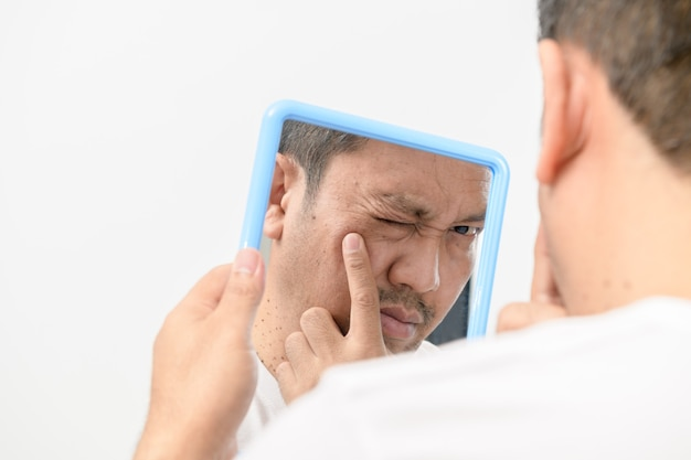 Een man van middelbare leeftijd die in de spiegel kijkt en zich zorgen maakt over puistjes en rimpels op zijn gezicht op witte muur, gezondheidszorgconcept