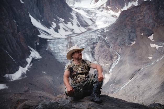 Een man van middelbare leeftijd in een cowboyhoed zit op een rots tegen een gletsjer en een berg