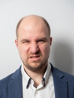 Een man van middelbare leeftijd in een pak kijkt vol afschuw naar de camera. mannelijk portret, emotie