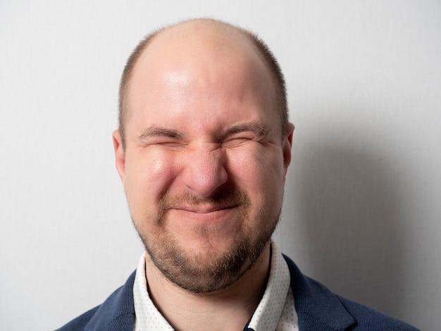 Een man van middelbare leeftijd in een pak op een grijze achtergrond. de ogen zijn strak samengedrukt. gespannen uitdrukking, scheel. emoties