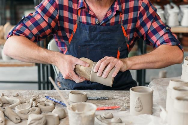 Een man van middelbare leeftijd in een werkuniform veegt met een vochtige spons een kleivormige beker af in een grote creatieve pottenbakkerij.