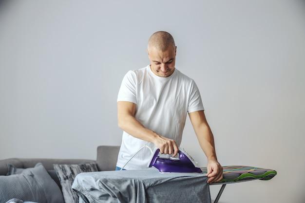 Een man van middelbare leeftijd in een wit t-shirt strijkt kleren in de woonkamer op een strijkplank. thuis, huis, moderne levensstijl