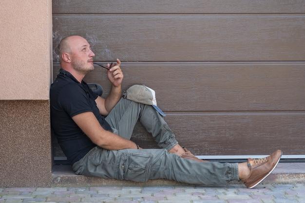 Een man van middelbare leeftijd rust op de stoep en rookt pijp. portret van blanke kale man, buitenshuis, close-up. slechte gewoonten, verslaving. ongezond levensstijlconcept. ruimte kopiëren
