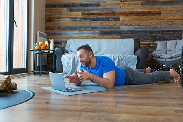 Een man van middelbare leeftijd tijdens een online videogesprek. hij ligt op de grond terwijl hij voor een laptopmonitor staat.