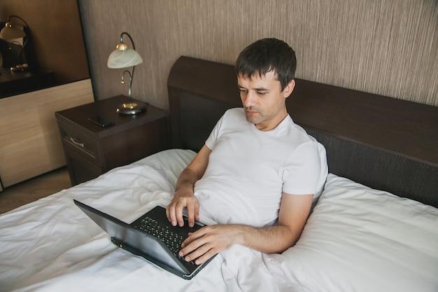 Een man van middelbare leeftijd zit in bed in zijn slaapkamer en werkt op een laptop. het concept van werken op afstand