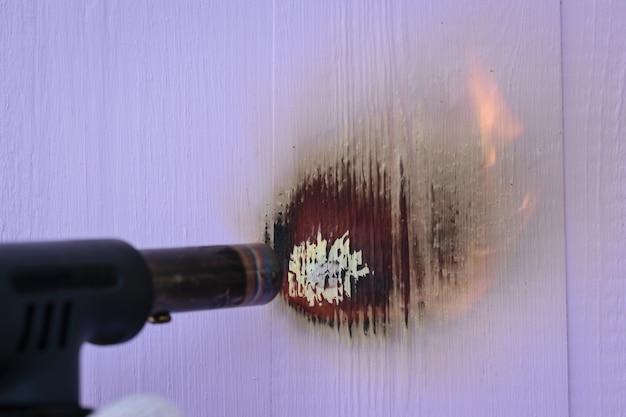 Een man verbrandt paarse houten planken met een gasbrander. behandeling van het houten oppervlakvuur.