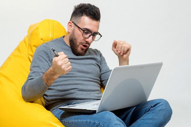 Een man verheugt zich tijdens het werken op laptop