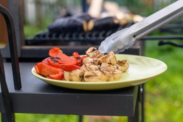 Een man verspreidt gegrilde paprika en champignons op een ronde keramische plaat met een keukentang