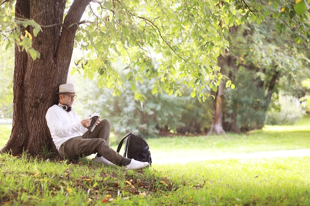 Een man verstopt zich op een warme dag in de schaduw van bomen. lunchpauze. rust midden op de werkdag.