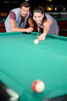 Een man vertelt een meisje hoe ze de bal correct moet slaan.