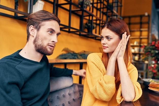 Een man vertelt iets aan een jonge vrouw in een trui aan een tafel in een café-interieur vrienden