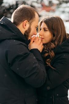 Een man verwarmt zachtjes de handen van zijn geliefde meisje bij koud weer