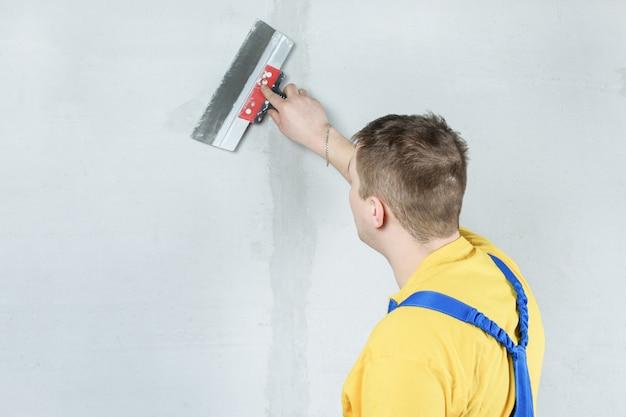Een man verwerkt de muur met een spatel. stukadoor op het werk.