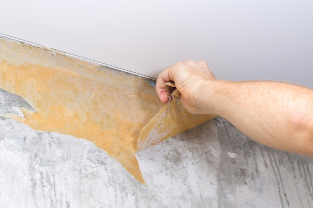 Een man verwijdert oud behang met een spatel en een spuitfles met water.