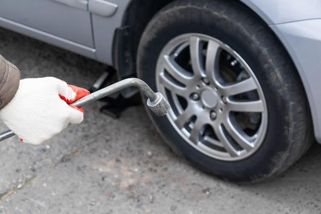 Een man verwisselt de zomerbanden van de auto voor de winter