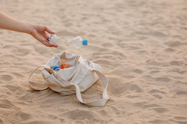 Een man verzamelt plastic flessen en afval op het strand op een openbare plaats, milieuvriendelijk en zorgzaam