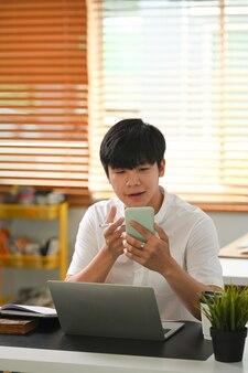 Een man videoconferentie met smartphone op kantoor aan huis.