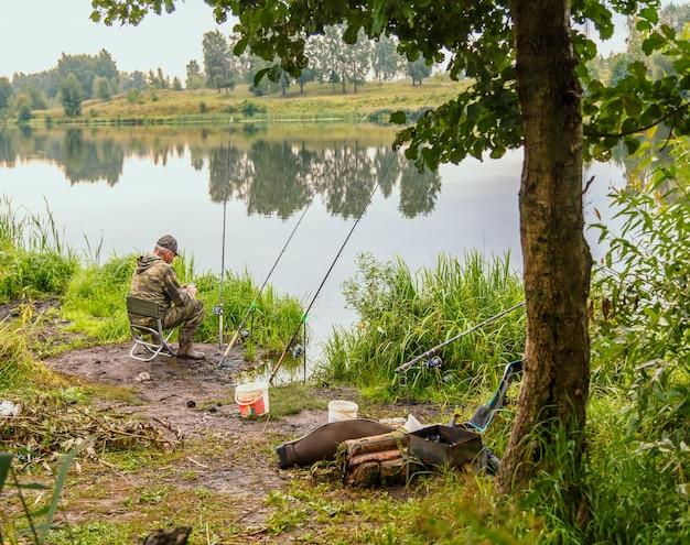 Een man visser met een hengel op de oever van de rivier op een zonnige dag is aan het vissen. horizontale foto