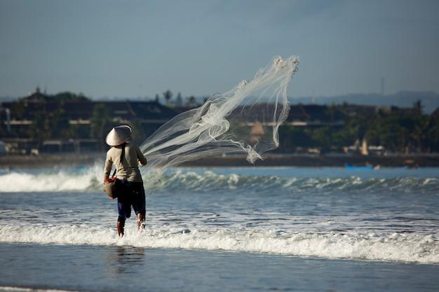 Een man vist met een net