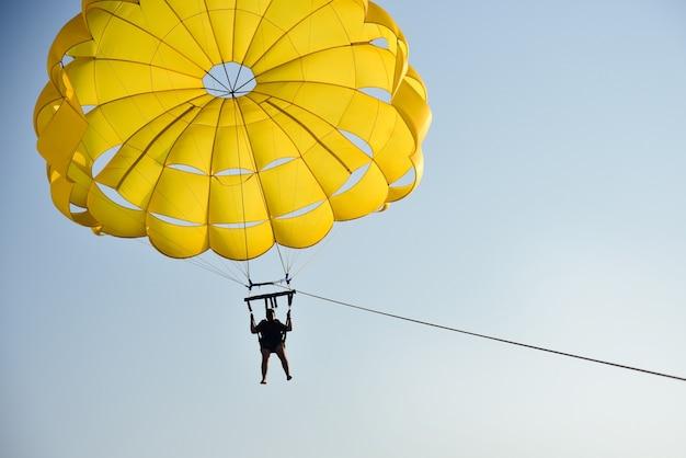 Een man vliegt een parachute over de zee bij zonsondergang