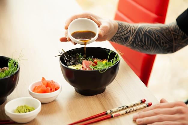 Een man voegt sojasaus toe om salade te prikken een mans hand giet sojasaus in een kom salade man jongeman dr...