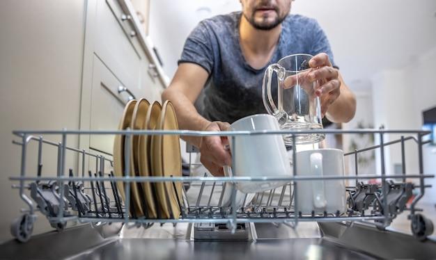 Een man voor een open vaatwasser zet borden neer of zet ze neer.