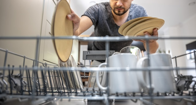 Een man voor een open vaatwasser zet borden neer of zet ze neer. Gratis Foto