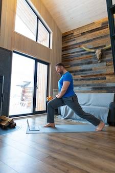 Een man warmt zijn spieren op voordat hij gaat trainen. online training met een tutorial van internet. gezond levensstijlconcept.
