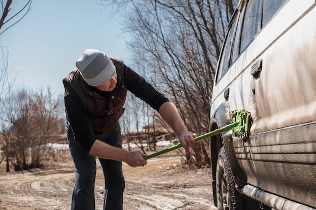 Een man wast de witte, vuile auto buitenshuis.