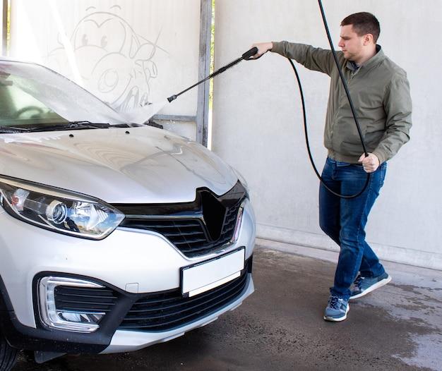 Een man wast een auto bij een contactloze wasstraat de auto van vuil wassen met poeder en schuim