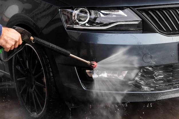 Een man wast een auto bij zelfbedieningswasstraat. hogedrukreiniger voor voertuigen, schoon te maken met water. car wash apparatuur, mlada boleslav,