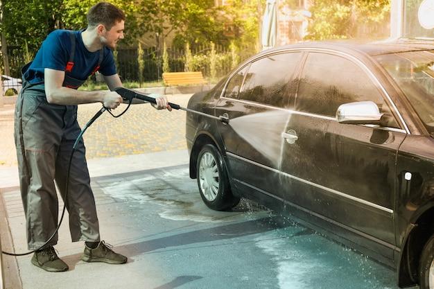 Een man wast een auto in een handmatige wasstraat.