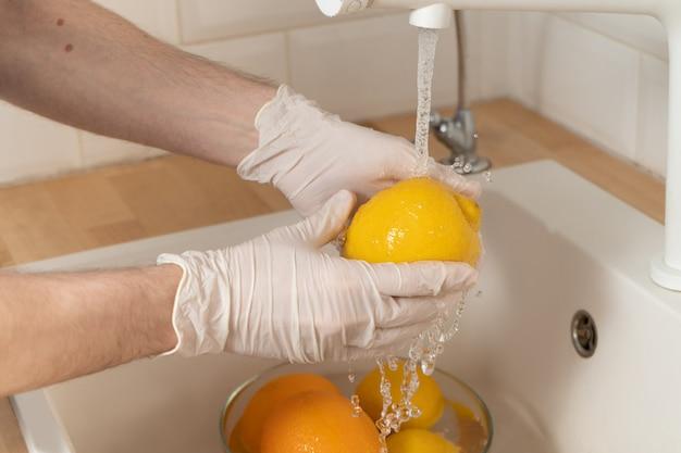 Een man wast een citroen met een wasmiddel in handschoenen. een jonge man steriliseert groenten en fruit tijdens een epidemie. handen in wegwerphandschoenen close-up was een citroen onder stromend water.