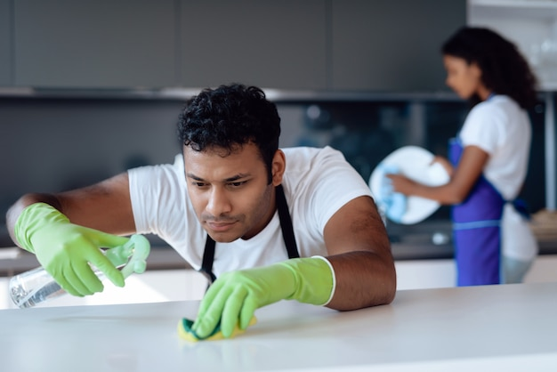 Een man wast het aanrecht met wasmiddel