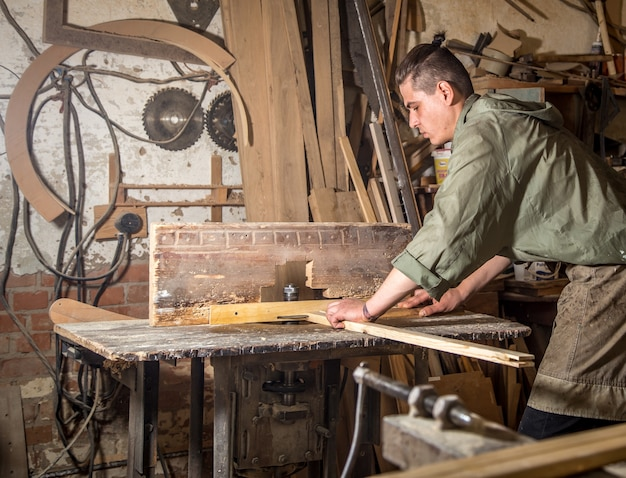 Een man werkt aan de machine met de vervaardiging van houten producten