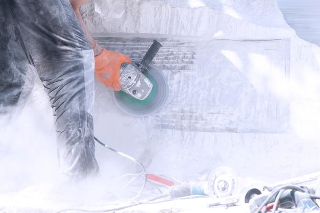 Een man werkt aan een monument van witte steen. slijpwerkzaamheden.