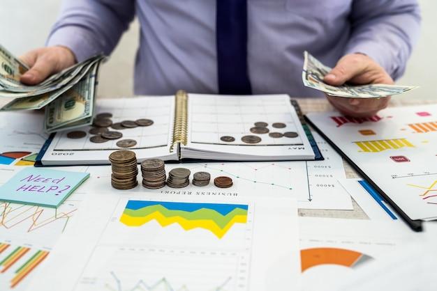 Een man werkt en berekent bedrijfswinsten uit de verkoop of lease van goederen of diensten en kantoor met behulp van grafieken en grafiekdocumenten, dollars en penningen