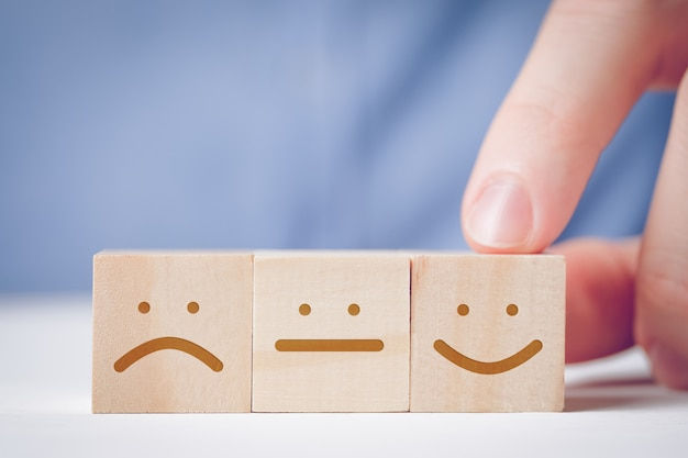 Een man wijst met zijn vinger naar een houten kubus met een positief gezicht naast een neutraal en ontevreden. voor het evalueren van een actie of resource.