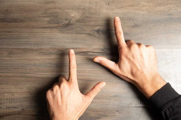 Een man wijst met zijn vingers op een houten tafel