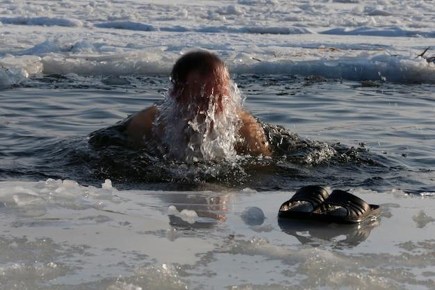 Een man wordt ondergedompeld in een ijsgat. badend in ijswater. de doop van jezus. religieuze vakantie