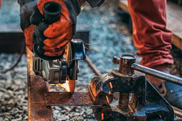 Een man zaagt metaal met een haakse slijper